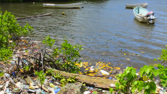 Pohnpei Micronesia horrible litter garbage next to boats on water at local homes used for fishing