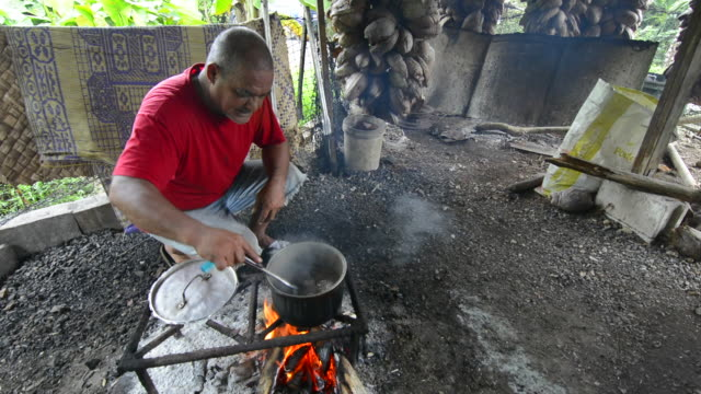 Pohnpei Micronesia local man cooking chicken in his small home with smoke