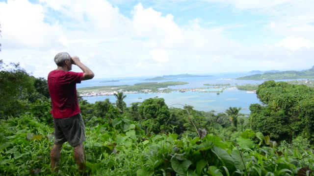 Pohnpei Micronesia man with binoculars looking at city of Kolonia from famous Sokehs Ridge