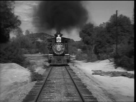 B/W REAR point of view 1800s steam train coming toward camera in countryside