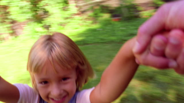 MS point of view adult's arms holding smiling blond girl spinning in air outdoors