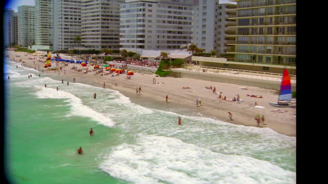 vidéos et rushes de aerial point of view along coastline with people on beach + swimming in ocean / miami beach, fl - terre en vue