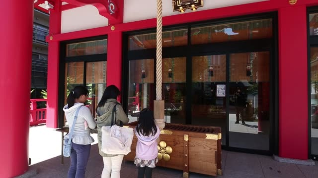 point of view , approaching the narukoten shrine next to a high-rise residential building in tokyo, japan, on monday, april 10 visitors ring a bell... - shrine stock videos & royalty-free footage