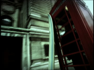high contrast point of view around red telephone booth with surfboard leaning on outside + person inside /london - telefonzelle stock-videos und b-roll-filmmaterial
