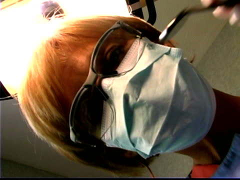 point of view as a dental hygienist leans in and uses a mirror and a dental pick on the viewer. - nur frauen über 40 stock-videos und b-roll-filmmaterial