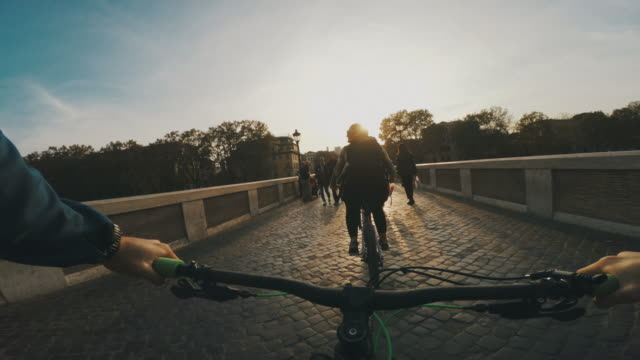 Point of view POV bicycle on Tiber bridge in Rome