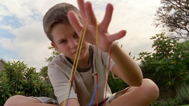 Point of view boy holding cat's cradle string figure up to CAM