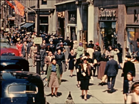 1941 point of view crowd walking past shops on Fifth Avenue, NYC / industrial