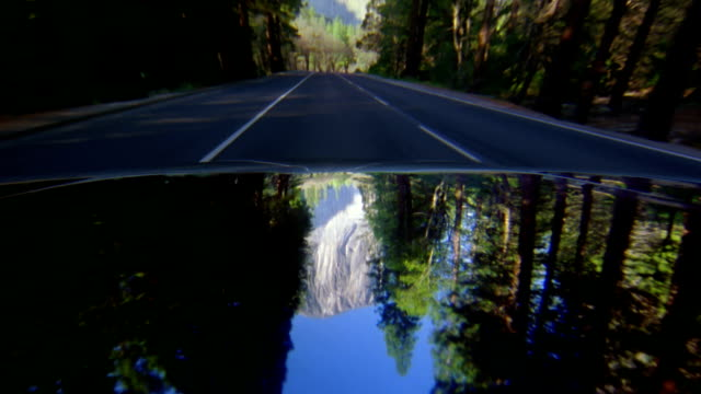 car point of view driving along road through yosemite national park / el capitan in reflection - el capitan yosemite national park stock videos and b-roll footage