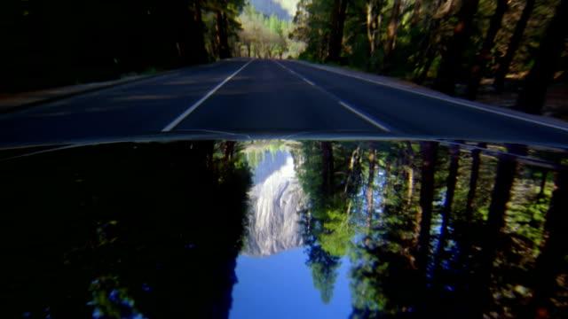 car point of view driving along road through yosemite national park / el capitan in reflection - el capitan kino stock-videos und b-roll-filmmaterial