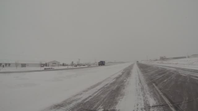 vidéos et rushes de point of view driving on a snow covered highway in a midwest downtown on an overcast winter grey day during a winter storm warning and hazardous traveling. - dakota du nord