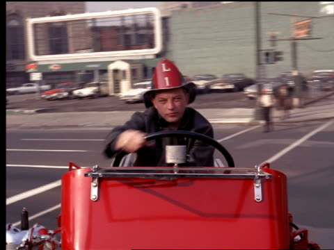 1965 rear point of view fireman driving back of hook and ladder fire truck in traffic on city streets - hook stock videos and b-roll footage