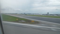 Point of view from airplane window landing on airport runway after flight