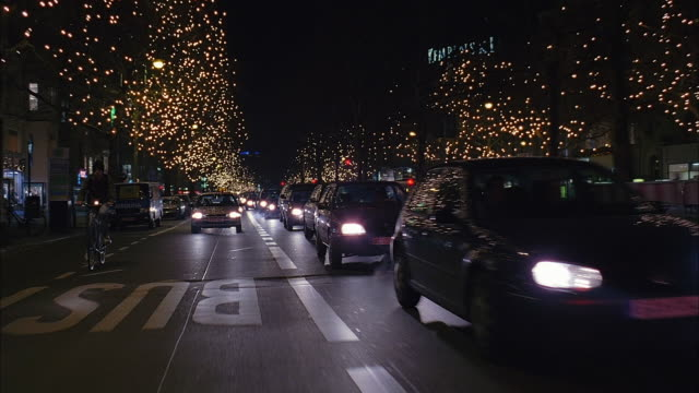 point of view from rear of car driving down bus lane of the kurfurstendamm with trees lit up at night / berlin, germany - londonalight点の映像素材/bロール