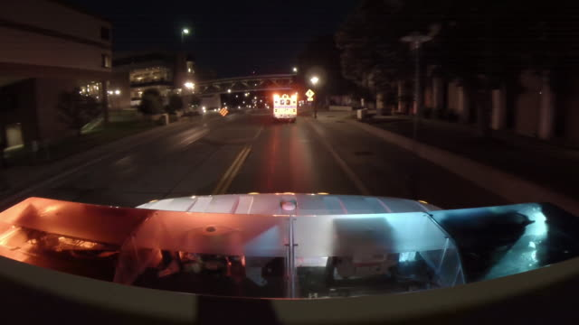 Point of view from the top of an emergency ambulance following a second ambulance, racing down the street to an urban hospital at night with flashing lights at the bottom of frame.
