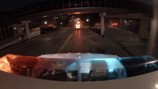 point of view from the top of an emergency ambulance following a second ambulance, racing down the street to an urban hospital at night with flashing lights at the bottom of frame. - flash stock videos & royalty-free footage