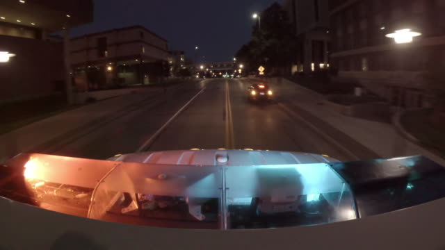 Point of view from the top of an emergency ambulance racing down the street to an urban hospital at night with flashing lights at the bottom of frame.