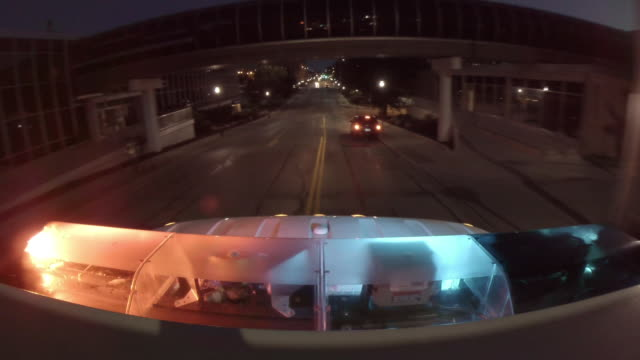 point of view from the top of an emergency ambulance racing down the street to an urban hospital at night with flashing lights at the bottom of frame. - ambulance stock videos & royalty-free footage