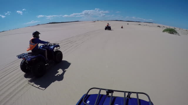 point of view from travelling bike quad bikes riding on sand dunes beach in the back ground several bikes drive along the beach in a row clear blue... - quadbike stock videos & royalty-free footage