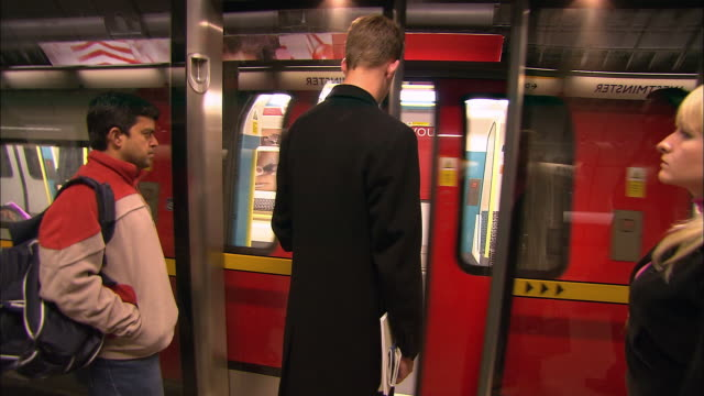 point of view getting on tube train behind other commuters at westminster station / london - imbarcarsi video stock e b–roll