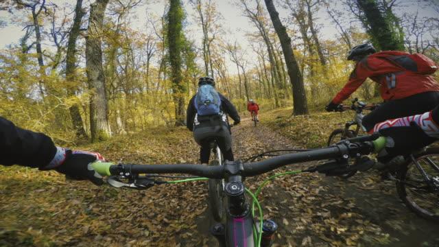 vidéos et rushes de point de vue de pov: groupe d'amis mountainbike dans la forêt. - vtt