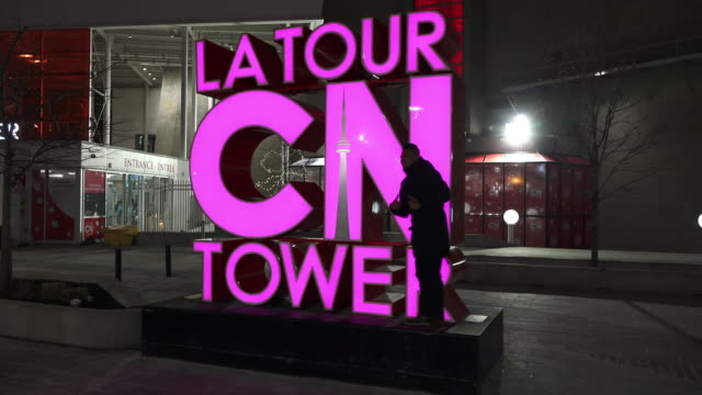 Point of view image of a person walking by the CN Tower Tour sign which is illuminated in purple Incidental people have their picture taken in the...