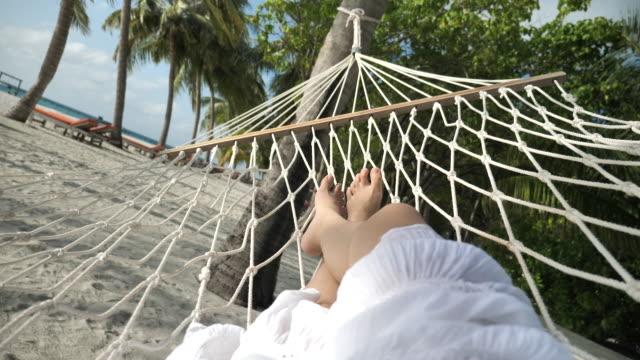 synpunkt ben av kvinnan koppla av i hängmatta på sommarlov på stranden - hängmatta sol bildbanksvideor och videomaterial från bakom kulisserna