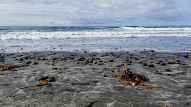 vidéos et rushes de 4k point of view low angle tilt up from sandy beach to surfers - caméra à l'épaule