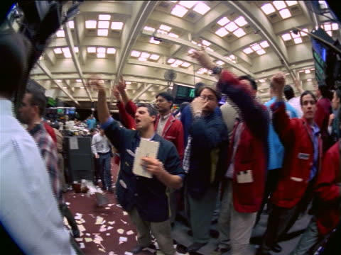 FISHEYE point of view male traders crowded together making hand signals on floor of Commodities Exchange, NYC