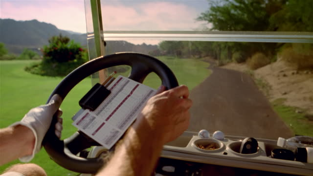 point of view man driving golf cart along path at golf course and onto green - golf cart stock videos & royalty-free footage