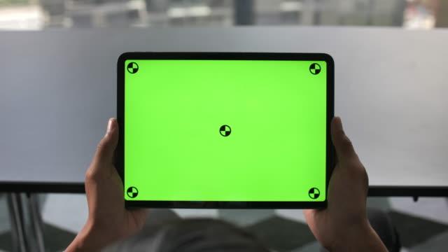 Standpunkt Mann hält DigitalTablet in der Hand und Blick auf Tablet PC green screen