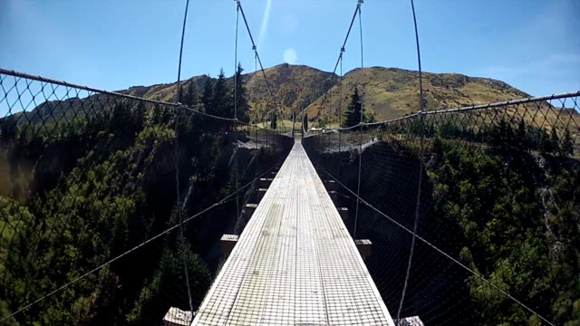 point of view of a cyclist crossing a suspension bridge - queenstown stock videos & royalty-free footage