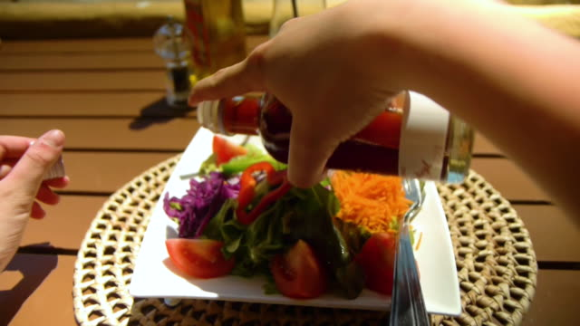 point of view of a woman's hand pouring olive oil over her salad at a back bar. - salad oil stock videos & royalty-free footage