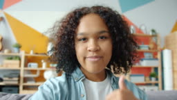 Point of view of Afro-American girl taking selfie smiling looking at camera at home