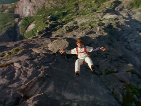 point of view of base jumper free falling past rocky cliff / Stavanger, Norway
