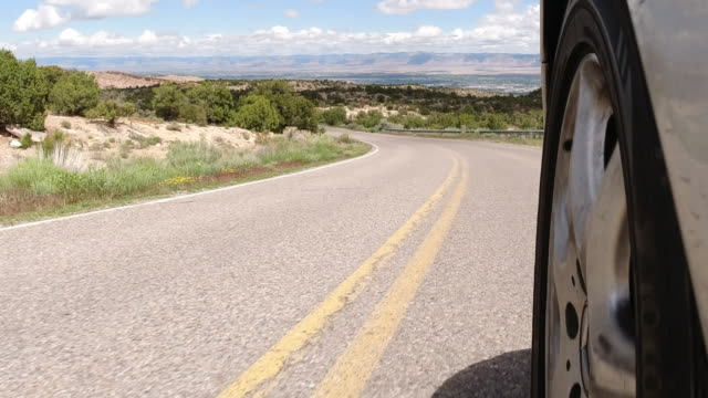 vídeos de stock e filmes b-roll de point of view of from the side of a silver vehicle while driving down the colorado national monument with fruita and grand junction, colorado in the background under a partly cloudy sky - road junction