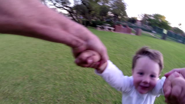 point of view of parent swinging child around in park - oscillare video stock e b–roll