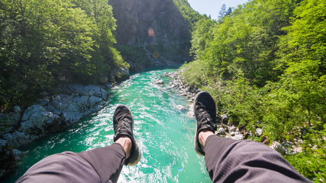 vidéos et rushes de point de vue d'une personne assise sur un pont suspendu, regardant le soufflet du ruisseau de montagne, pendant avec les pieds - assis