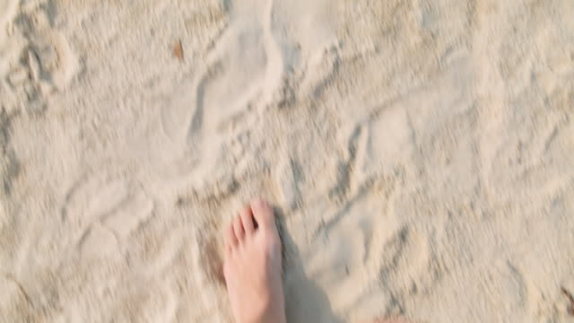 Point of View (POV) of the woman feet walking in the sand at Byron Bay