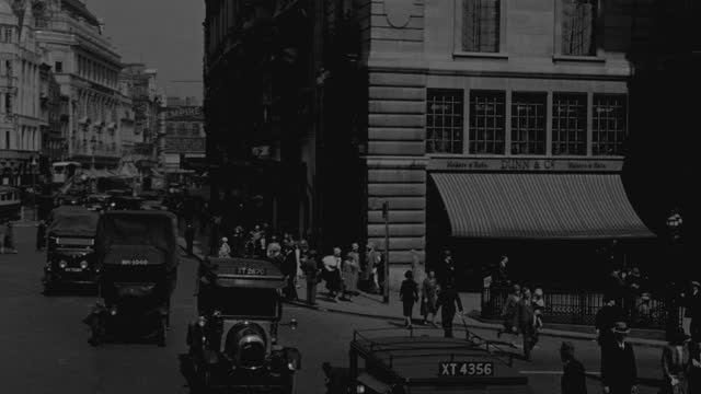 "point of view of traffic and pedestrians on busy piccadilly circus in city, ""cochran's 1930 revue"" sign on building by street, london, uk - 1930 stock videos & royalty-free footage"