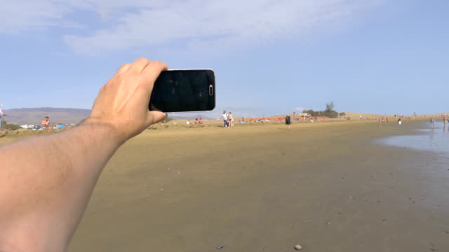 Point of view on the taking a selfie photo  in Maspalomas beach Grand Canary in 4K