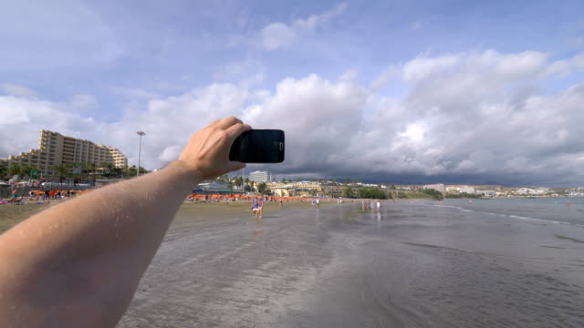 Point of view on the taking a selfie photo in Playa del Ingles beach in Canary Island  in slow motion 4k