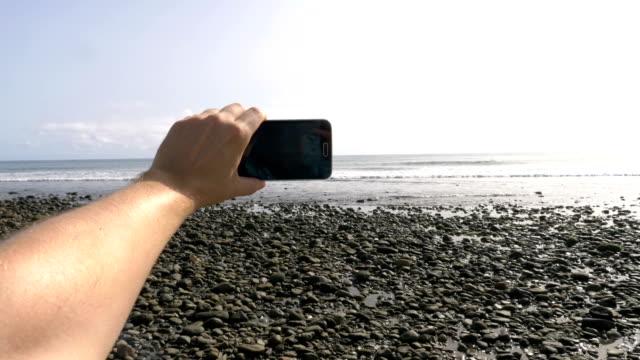 Synpunkt på att ta en selfie foto på steniga stranden i Spanien i 4K