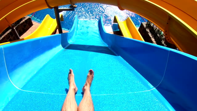 Point of view on the water slide in the water park in slow motion