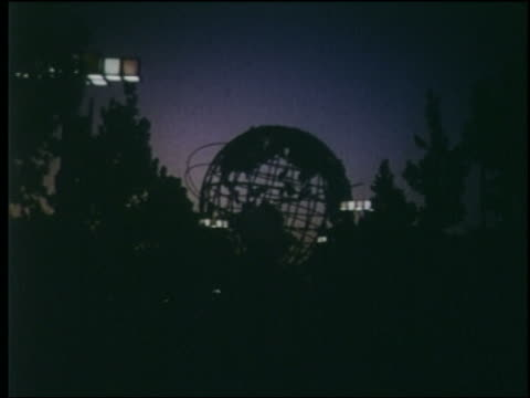 1964 point of view on treelined promenade toward Unisphere at dusk / NY World's Fair
