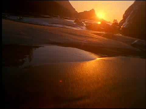 vídeos y material grabado en eventos de stock de point of view over beach with rocks at sunset - cincuenta segundos o más
