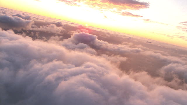 vídeos de stock e filmes b-roll de aerial point of view over clouds with sunset on horizon - paisagem com nuvens