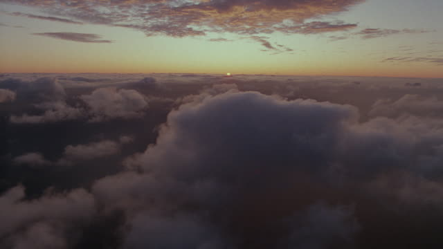 AERIAL point of view over clouds with sunset on horizon