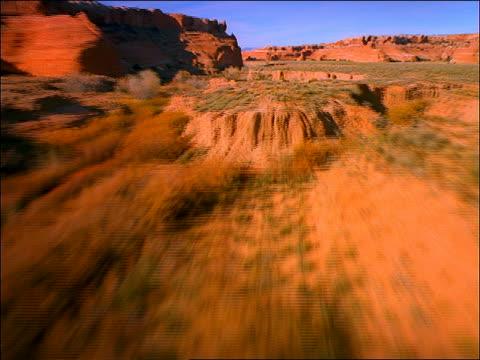 vidéos et rushes de aerial point of view over desert with bushes + plants lined by buttes / utah - piton rocheux