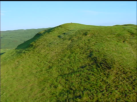 aerial point of view over green hill to woman in black dress + hat relaxing on top / oban, argyll, scotland - black dress stock videos & royalty-free footage